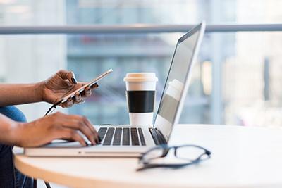 afbeelding van een bureau met laptop en een kop koffie. Er is ook een vrouwenhand in beeld.