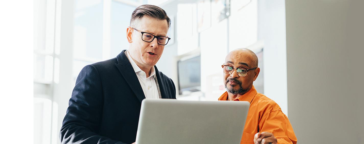 afbeelding van twee technici die met elkaara overleggen, terwijl ze samen naar een laptop kijken.